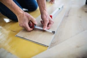 A midsection of senior man laying vinyl flooring, a new home concept.